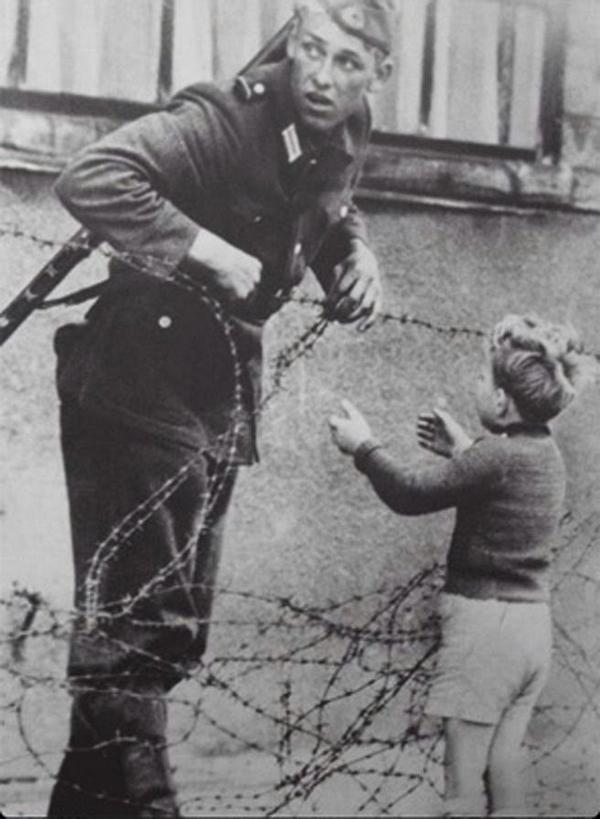 Східно- німецький солдат допомагає хлопчику перетнути новостворену Берлінську стіну, 1961